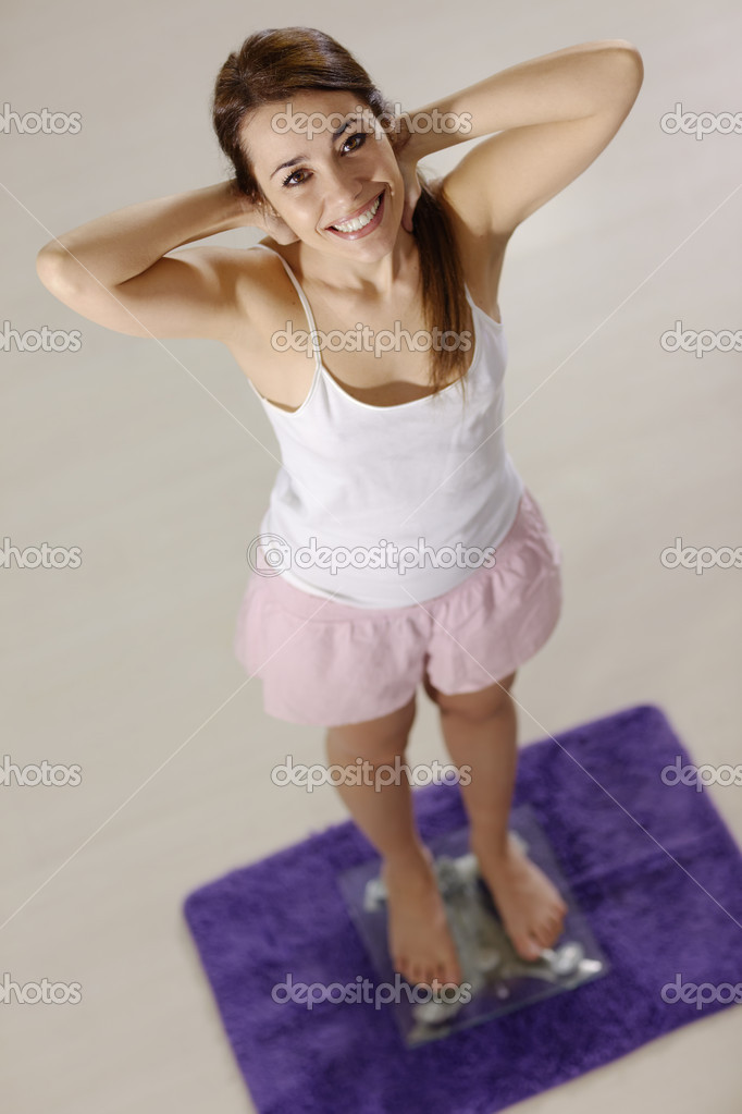 Mid adult happy caucasian woman on scales at home expressing satisfaction and joy for losing weight. High angle view — Stock Photo #9757354
