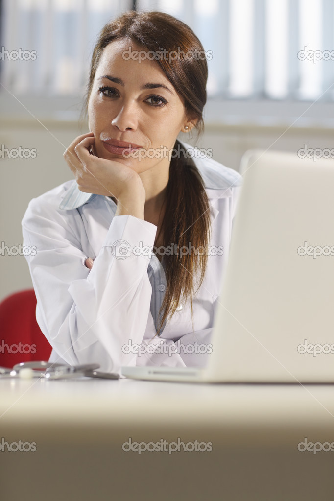 Portrait of mid adult attractive woman smiling at work as doctor with pc in hospital office. Copy space  Stock Photo #9757435