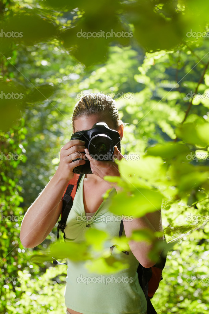 Young woman trekking among trees and taking pictures with dslr camera. Vertical shape, front view, waist up — Stock Photo #9757989
