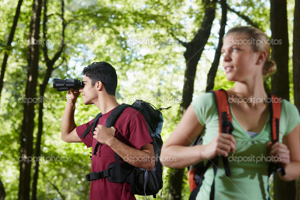 Young trekking among trees and looking at birds with binoculars. Horizontal shape, side view, waist up — Stock Photo #9758448