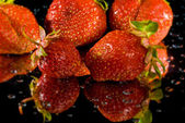 Strawberries on wet black background. — Stock Photo