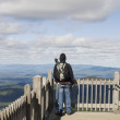 Man on viewpoint admiring landscape - Stock Photo