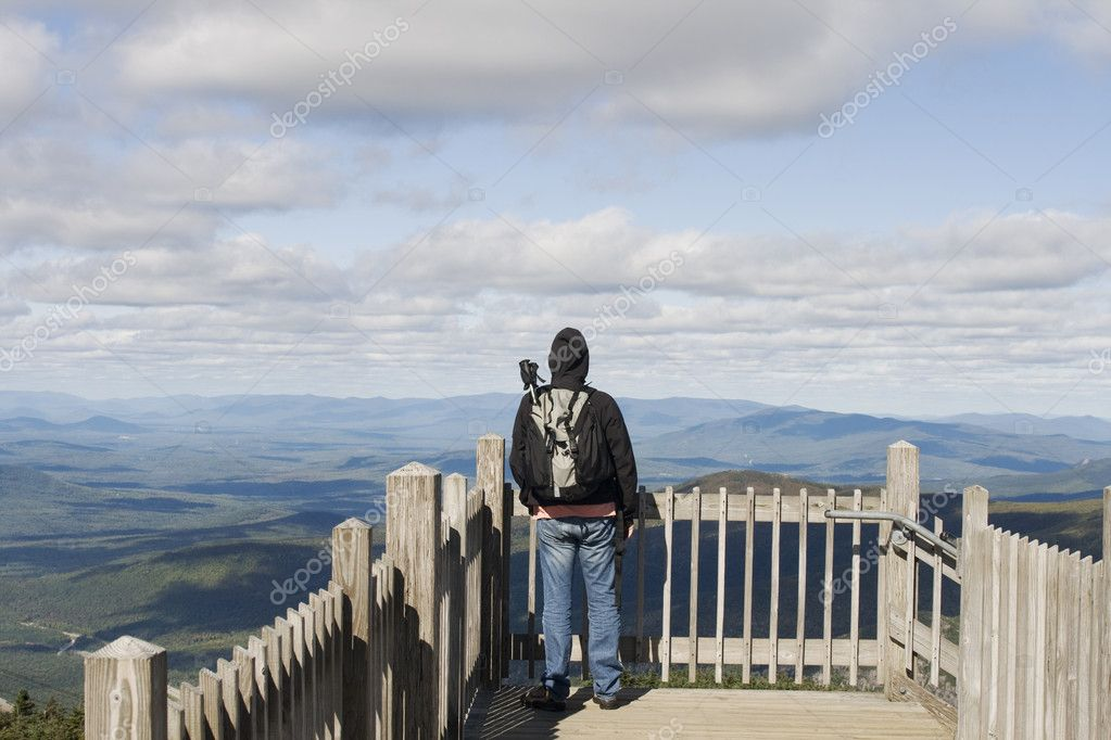 Man with backpack and hiking sticks admiring view — Stock Photo #8693751