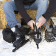 Man putting on ice skates - Stock Photo