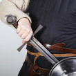Unsheating a medieval sword - Stock Photo