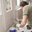 Painting a door white - Stock Photo