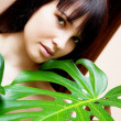 Girl with green leaves in garden - Stockfoto