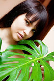 Girl with green leaves in garden — Stock Photo