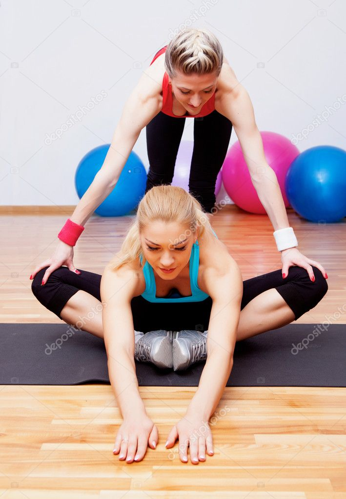 One girl helping another to stretch in fitness club — Stock Photo #10062254