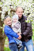Family in blossom garden — Stock Photo