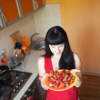 Girl with strawberry on the kitchen — Stock Photo