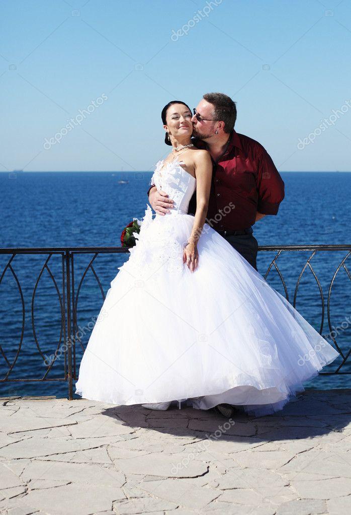 新娘和新郎在海边接吻