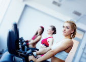 Three girls in fitness center — Stock Photo