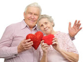Happy old couple with red hearts — Stock Photo