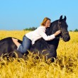 Beautiful woman rides and pets horse in field - Stock Photo
