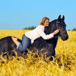 Stock Photo: Beautiful womrides and pets horse in field