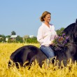 Beautiful smiling woman rides pretty horse in field — Stok fotoğraf