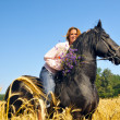 Beautiful smiling woman rides pretty black horse in field — Stock Photo #8883746