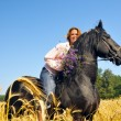 Beautiful smiling woman rides pretty black horse in field - Stock Photo