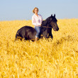 Beautiful woman rides a pretty horse in field — Stock Photo #8883748