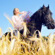 Beautiful woman rides pretty horse in summer field and takes a s — Stock Photo