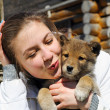 Young beautiful girl kisses a puppy — Stock Photo