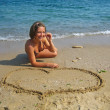 Beautiful girl drawing heart on sand — Stock Photo