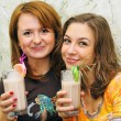 Two beautiful laughing girls drink cocktails with fruits - Stock Photo