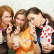 Three attractive girl eating fruit candies - Zdjcie stockowe