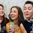 Three beautiful joyful young girls drink cocktails with fruits — Stock Photo