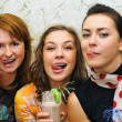 Three beautiful fresh joyful young girls drink cocktails with fr — Stock Photo