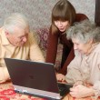 Foto Stock: Grandparents and granddaughter looking to the laptop