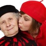 Granddaughter kiss grandmother cheek — Stock Photo #8884987