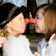 Stock Photo: Portrait of Granddaughter and granny with clown noses nose-to-no