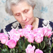 Portrait of granny behind bouquet of pink rose — Stock Photo