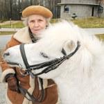 Happy grandmother with white pony — Stock Photo #8885665