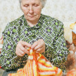 Spectacled old woman binds cardigan — Stock Photo #8885705