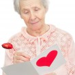 Senior woman hold post-card with heart shape on it cover — Stock Photo
