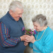 Happy old couple smell flowers — Stock Photo #8886011