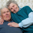 Happy smiling old couple sitting together in each other's embrac — Stock Photo #8886013