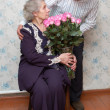 Stock Photo: Old couple and big bouquet of pink roses