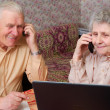 Senior couple gossip about something by phone - Stock Photo