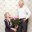 Happy old couple and big bouquet of pink roses — Stock Photo