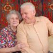 Seventy year old couple smiling at home - Stock Photo
