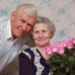 Happy old couple and bouqet of roses — Stock Photo
