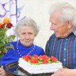 Elderly couple with tasty big cake — Stock Photo #8886331