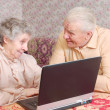 Stock Photo: Couple sit ar laptop and discuss