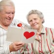 Happy old couple with post-card — Stock Photo