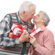 Stock Photo: Senior men give gifts senior women
