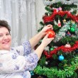 Elderly woman decorates Christmas tree — Stock Photo #8886501